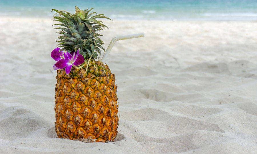 Tropical exotic pineapple cocktail at the beach overlooking the