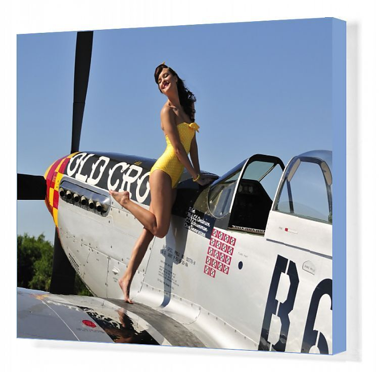 Beautiful 1940s style pin-up girl posing with a P-51 Mustang